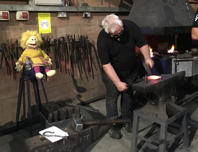 Einar watches Gary making his spearhead - just look at all those tools!