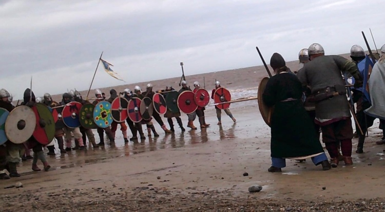 Viking reenactors lined up for battle on the beach