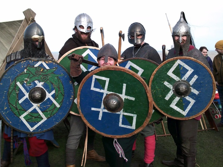 Some members of Odin's Aett Viking reenactment posing behind ther shields